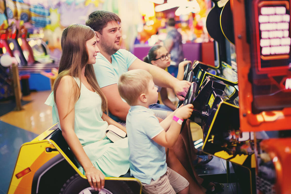Family playing racing arcade game