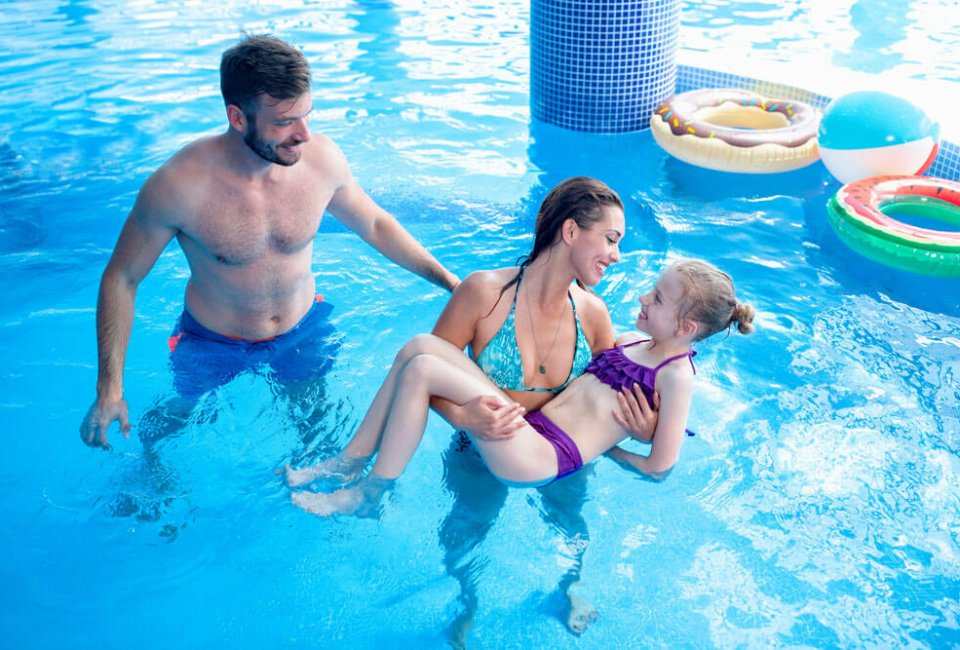 Small family enjoying open swim in a pool